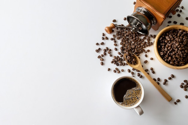 白いテーブルの上にホットコーヒー、豆、ハンドグラインダー。テキスト用のスペース。