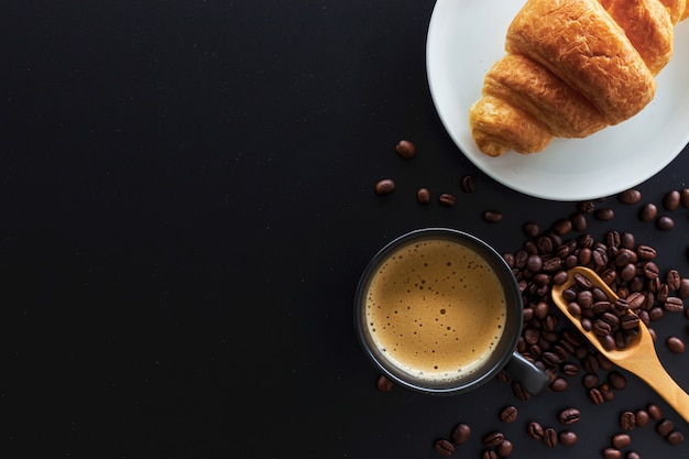 Hot coffee, bean and butter croissants on black table