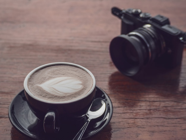 Hot coffee in black cup with camera