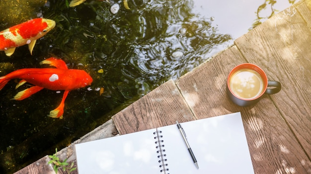 Hot coffee, book, and pen place near a fancy carp pond.