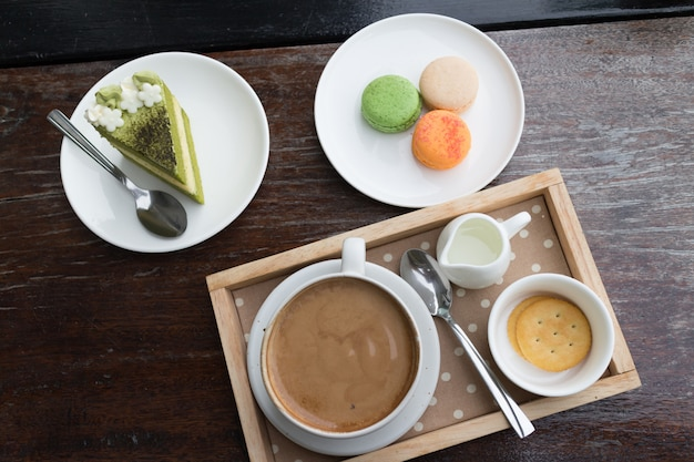 Hot coffee breakfast set with green tea cake and fresh macaroon in cozy outdoor cafe