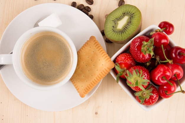 Hot coffee, cake and fruits on wooden table