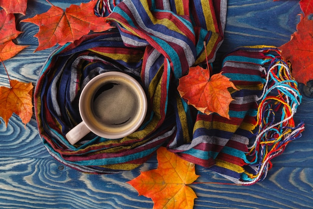 Hot coffee cappuccino, blanket and autumn leaves on old wooden surface