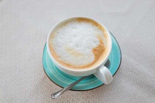 ベージュのテーブルに分離された翡翠色のカップのホットコーヒーカプチーノラテアート。カプチーノコーヒーカップの上面図。乳白色の泡のラテアート。緑色のセラミックマグカップで提供されるホットイタリアのエネルギー飲料