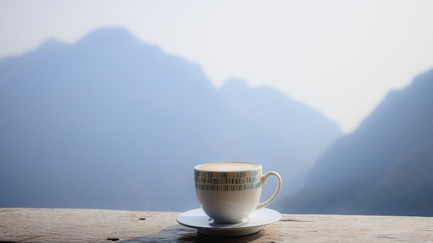 Hot coffee cappuccino in white cup on wooden terrace with beautiful scenic view nature background of misty morning mountain at phahee doi chiang rai thailand