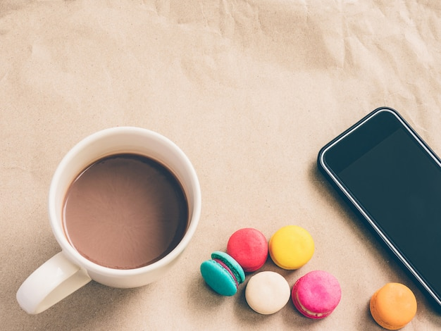 Hot coffee, colorful macaroons and smartphone