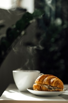 Hot coffee and a croissant on the table