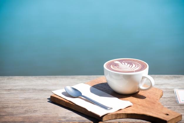 ホットコーヒーカップカプチーノアート、スプーン、ティッシュ、木製テーブル上のチョッピングボード