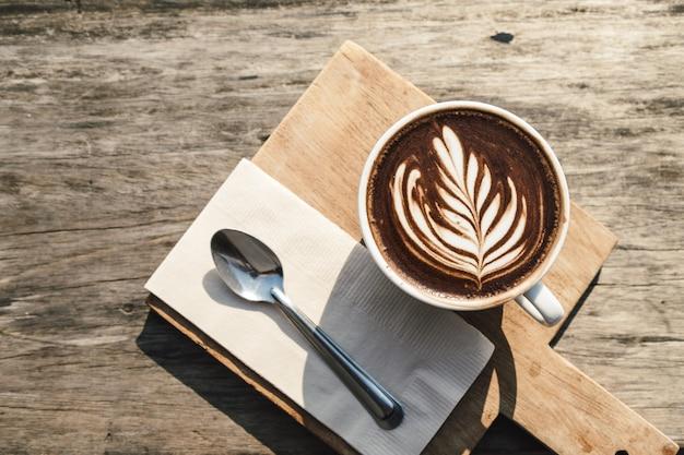 Hot coffee cup cappuccino art, spoon, tissue, chopping board