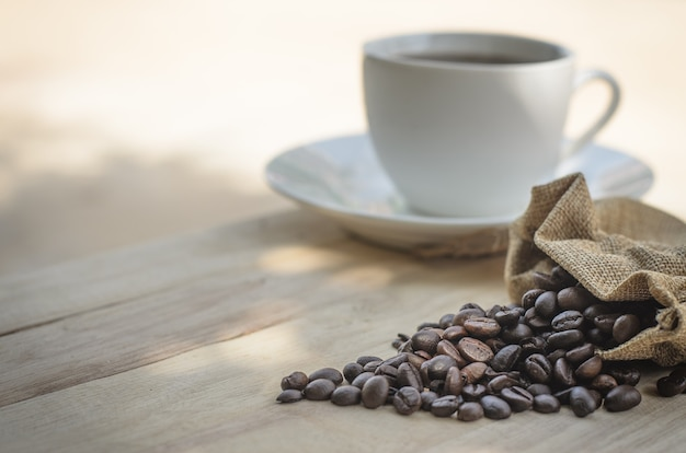 Hot coffee cup and coffee beans roasting on the wooden table in the morning