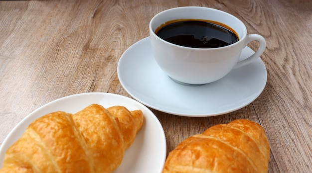 Hot coffee cup and croissant morning snack