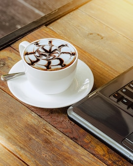 Hot coffee cup and laptop on wood table in the cafe.