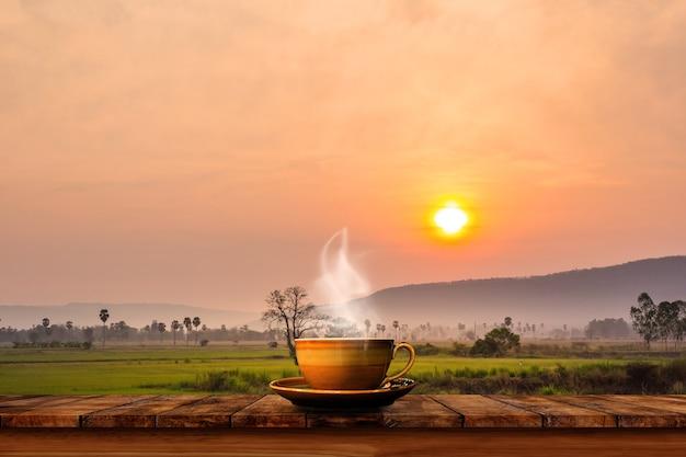 田んぼの背景と古い木のテーブルにホットコーヒーカップ。