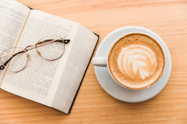 Hot coffee cup with cappuccino latte art and eyeglasses over an open book on table