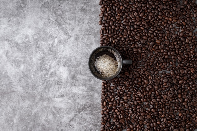 Hot coffee cup with coffee beans on cement wall background.