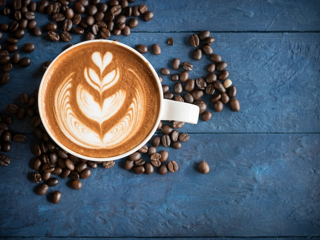 Hot coffee in a cup with foam milk beautiful latte art and coffee beans on blue wooden table background. cappuccino or latte with froth foam, drinks concept.