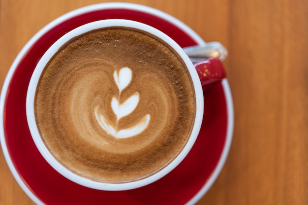 Hot coffee cup with latte art  in red cup on wood background,flat lay