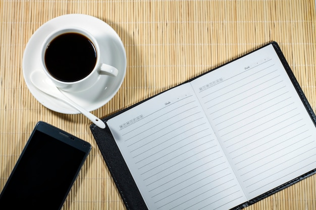 Hot coffee cup with notebook and mobile on the desk businessman