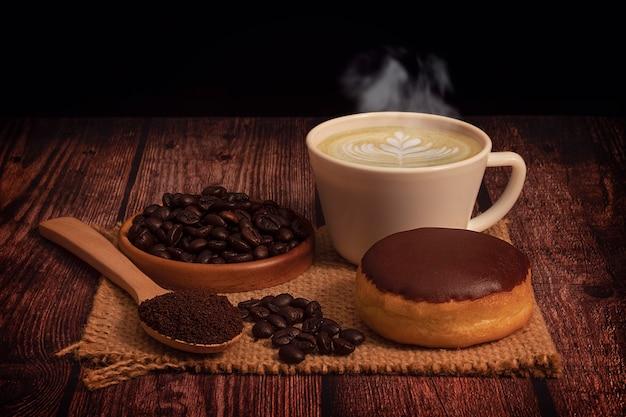木製のテーブルと黒の背景に有機コーヒー豆とホットコーヒーカップ