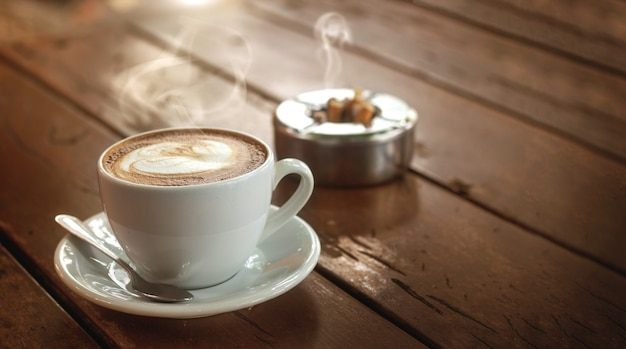 Hot coffee cup with smoke and cigarette on wood table in cafe