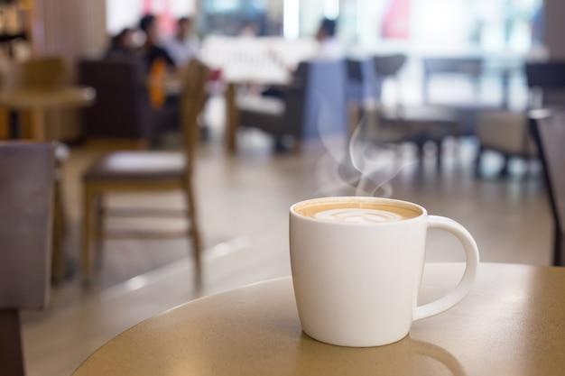 空の木製テーブルに煙とホットコーヒーカップ