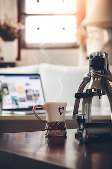 Hot of coffee cup with smoke on wooden table in living room.