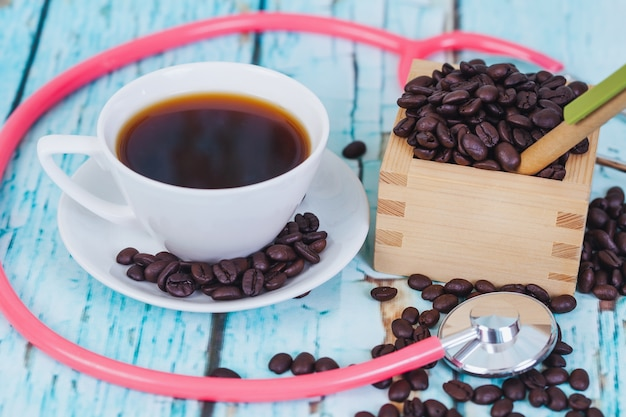 Hot coffee cup with stethoscope on wood table.