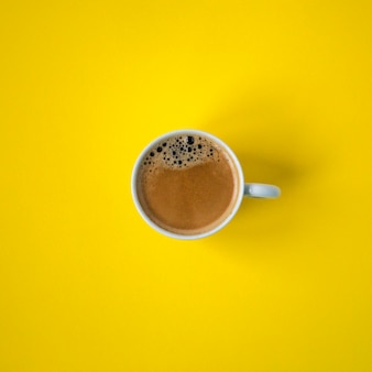 Hot coffee cup on yellow