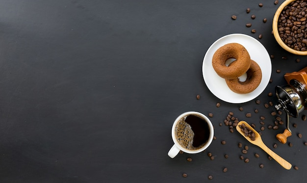 Hot coffee, donuts, bean and hand grinder on black table