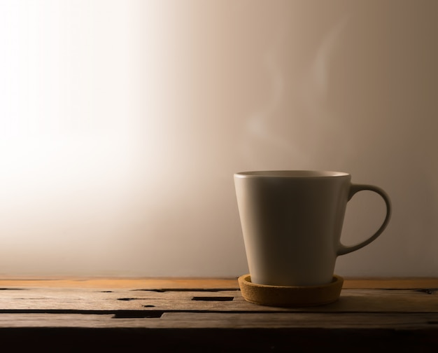 Hot coffee for early morning with warm light on table.