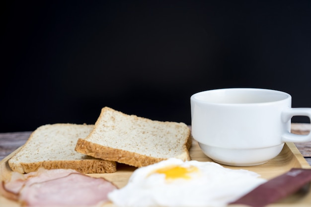 Hot coffee, egg, ham and bread on wooden table for breakfast with copy space