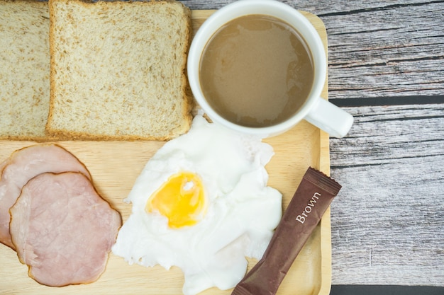 Hot coffee, egg, ham and bread on wooden table for breakfast