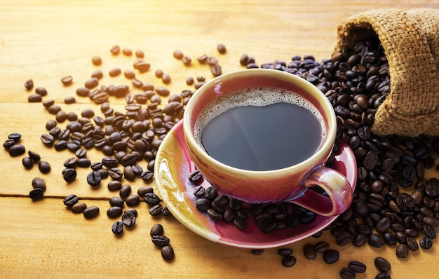 Hot coffee espresso or americano and coffee bean on older wood table at morning time. coffee break time.