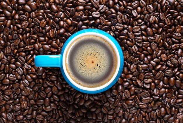 焙煎コーヒー豆の背景に青いカップのホットコーヒー。上面図、フラットレイ。