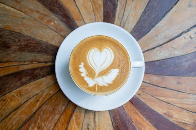 Горячий кофе в чашке на деревянном столе, латте-арт
