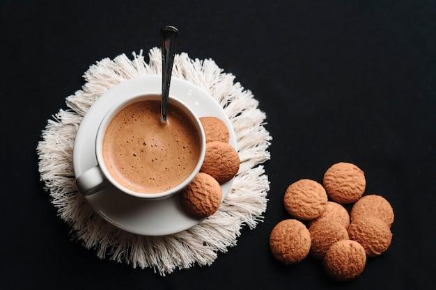 皿にクッキーを入れたカップに入ったホットコーヒー。スペースをコピーします。上面図。