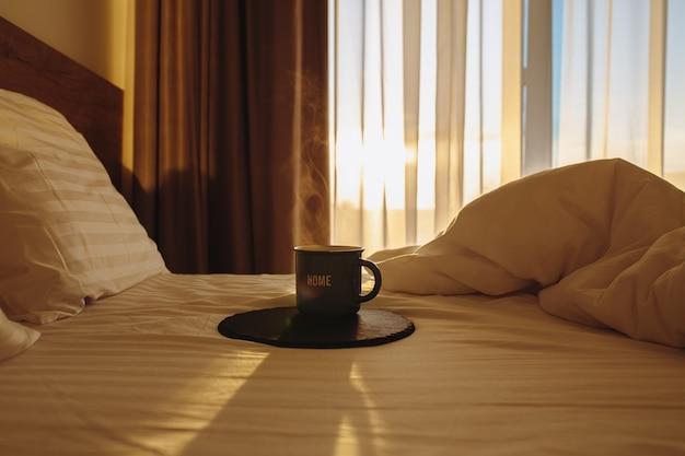ベッドの中でホットコーヒー白いベッドの中でホットコーヒーで目を覚ます太陽が寝室に輝いています