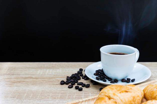 Горячий кофе в белой чашке с кофейными зернами и круассанами на деревянном столе, концепция завтрака