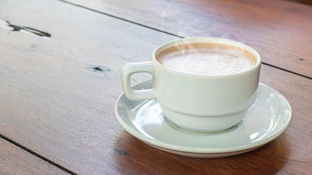 木製のテーブルの上の白いガラスのホットコーヒー