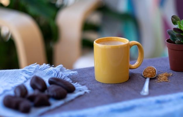植物と椅子の焦点がぼけたチョコレートとバルコニーで屋外の黄色いセラミックカップのホットコーヒー