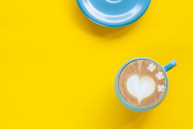 Hot coffee latte art heart on color background.