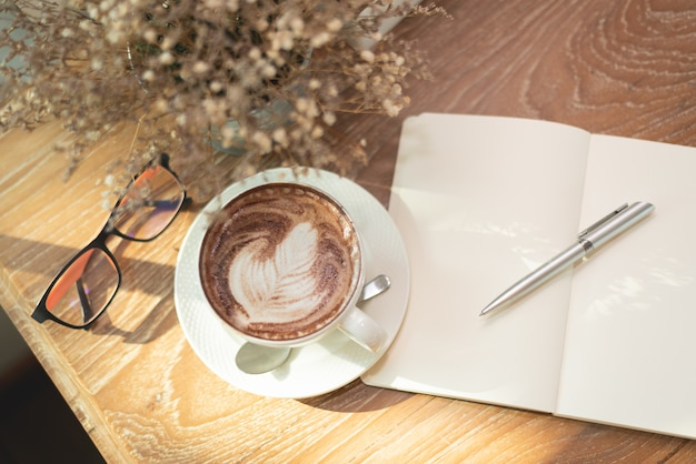 Hot coffee latte art, note book and glasses on wood table in the cafe