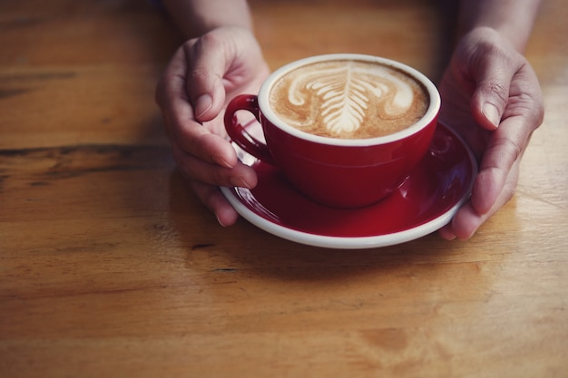 Hot coffee latte cappuccino in red cup and saucer with beautiful latte art milk foam on barista's hands holding serving on wood table background.