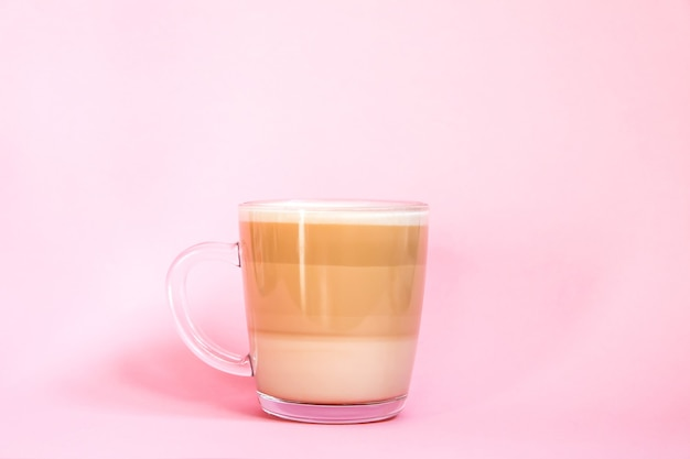 부드러운 분홍색 배경에 뜨거운 커피 라떼 투명 유리 컵.