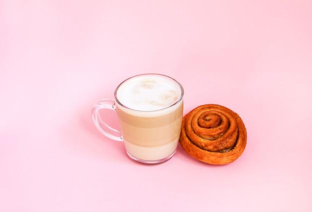 뜨거운 커피 라떼 투명 유리 컵과 분홍색 배경에 달콤한 계피 롤