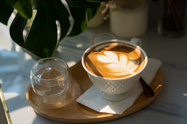 上面図の木製の机の上のカップマグカップにラテアートミルクフォームとホットコーヒーラテ。朝食としてカフェの喫茶店で、ビジネスワークコンセプト中