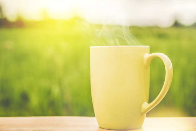 Hot coffee mug over nature green background