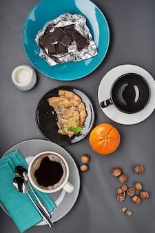 Горячий кофе, орехи, шоколад и печенье.