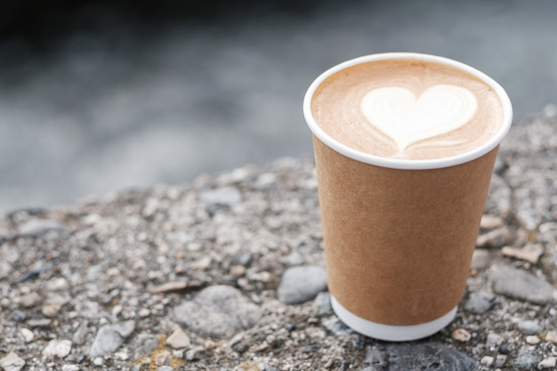 Hot coffee paper cup against river, heart shape latte coffee art. love, holiday, valentine day and free plastic container concept