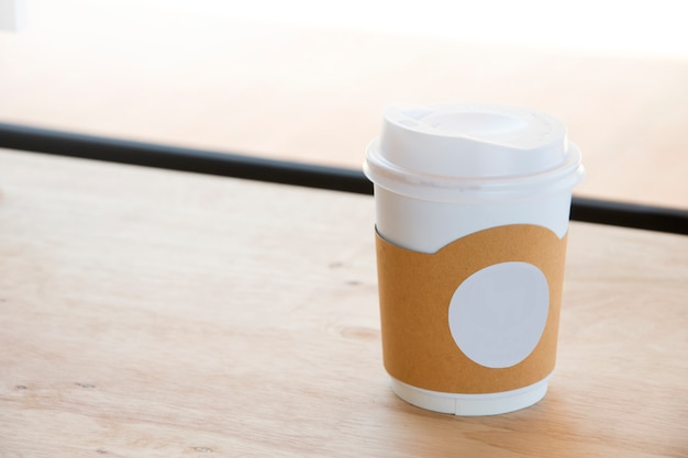 Hot coffee in paper cup isolated on wood table background.